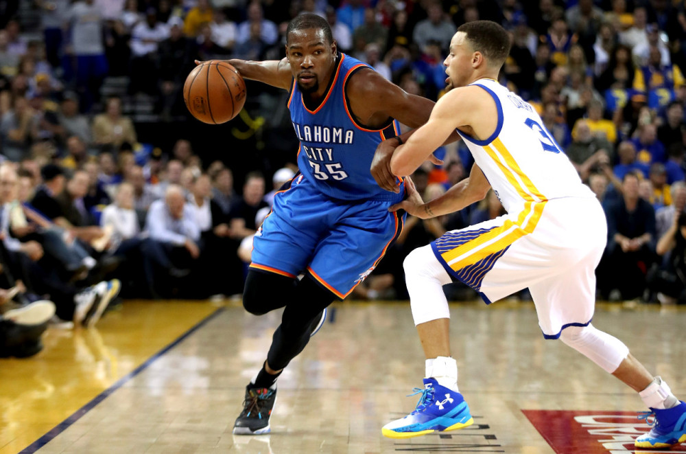 Kevin Durant of the Thunder driving right along the out of bounds line defended by Stephen Curry of the Warriors, 2016